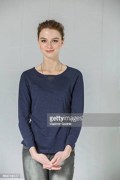 portrait of confident woman standing with hands clasped against white background - three quarter front view stock pictures, royalty-free photos & images