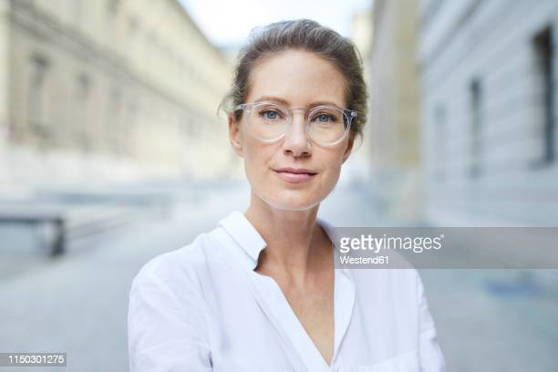 portrait of confident woman wearing glasses and white shirt in the city - selbstvertrauen stock-fotos und bilder