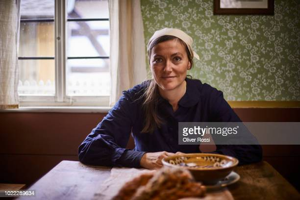 portrait of confident woman wearing headscarf sitting at table at home - hausfrau stock-fotos und bilder