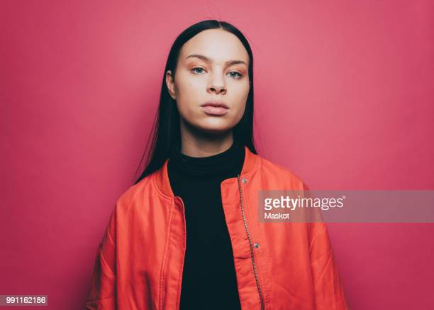 portrait of confident woman wearing orange jacket over pink background - attitude stock pictures, royalty-free photos & images