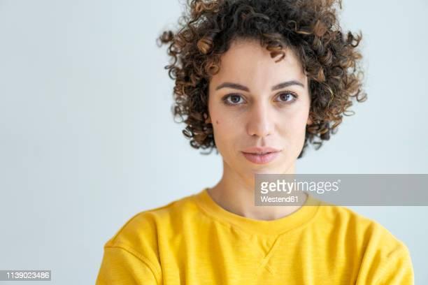 portrait of confident woman wearing yellow sweater - gelockt stock-fotos und bilder