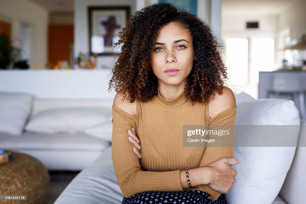 Portrait of confident woman with arms crossed sitting on sofa at home : Stock Photo