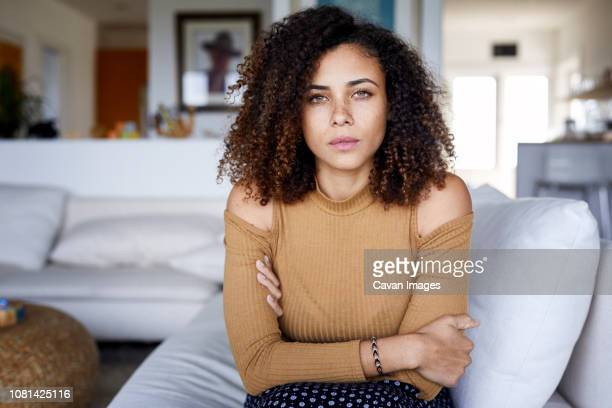 Portrait of confident woman with arms crossed sitting on sofa at home