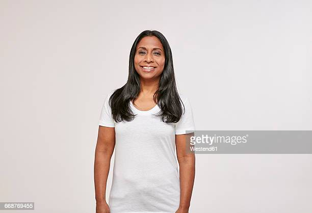 Portrait of confident woman with black hair wearing white t-shirt