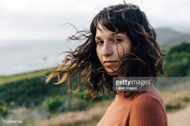 portrait of confident woman with freckles standing against sky - natur stock-fotos und bilder