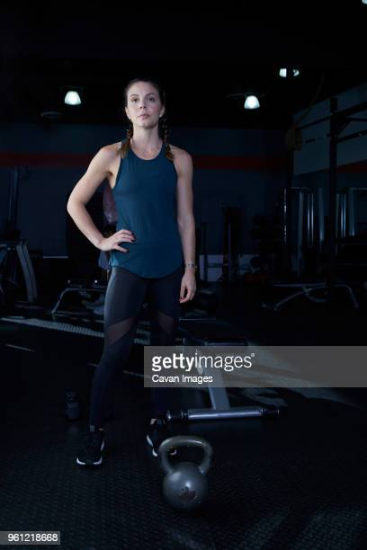portrait of confident woman with hand on hip standing by exercise equipment at gym - main sur la hanche photos et images de collection