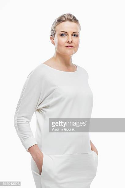 portrait of confident woman with hands in pockets against white background - mains dans les poches photos et images de collection