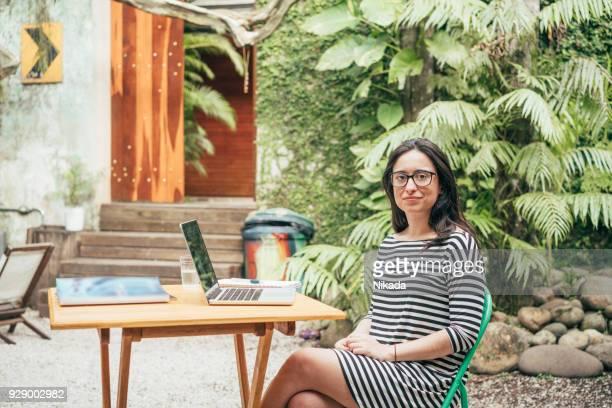 Porträt der selbstbewusste Frau mit Laptop am Tisch draußen Kreativbüro