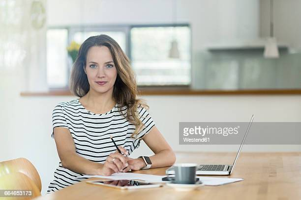Portrait of confident woman with laptop at table