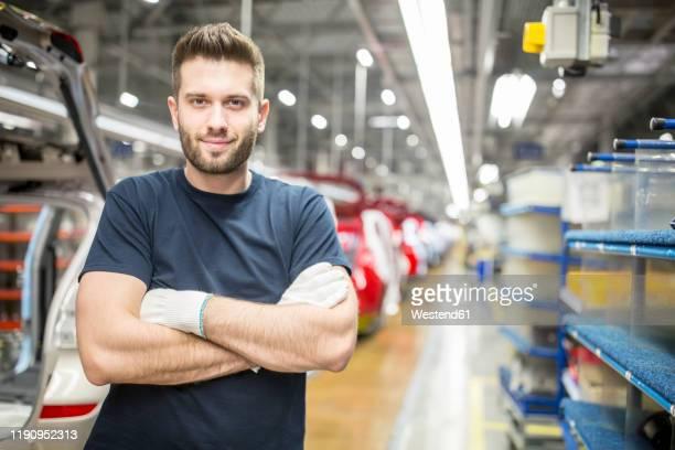 portrait of confident worker in modern car factory - industrieberuf stock-fotos und bilder