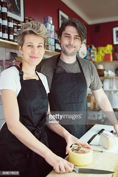 Portrait of confident workers at counter in supermarket
