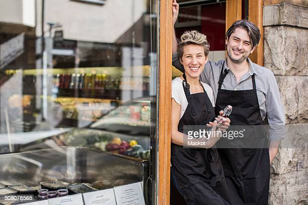 Portrait of confident workers standing at supermarket entrance