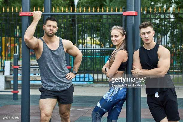 Portrait of confident young athletes standing by horizontal bar