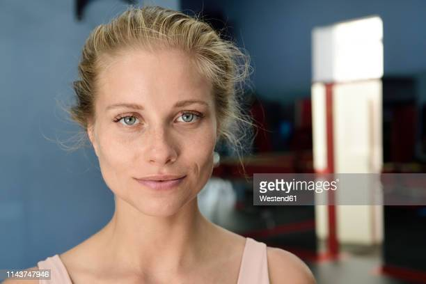 portrait of confident young blond woman in a gym - blue eyes stock pictures, royalty-free photos & images