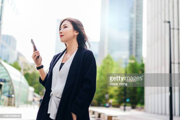 portrait of confident young business woman with smartphone - asian and indian ethnicities stock pictures, royalty-free photos & images