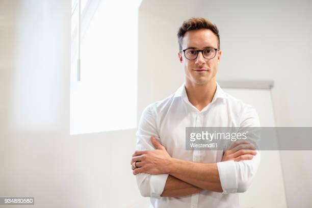 portrait of confident young businessman in office - vêtement de peau photos et images de collection