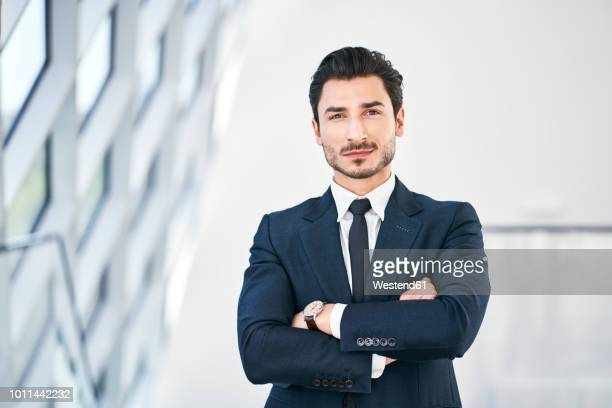 portrait of confident young businessman - arme verschränkt stock-fotos und bilder