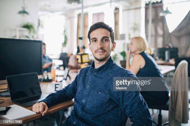 portrait of confident young businessman sitting at desk in creative office - personas en el fondo fotografías e imágenes de stock