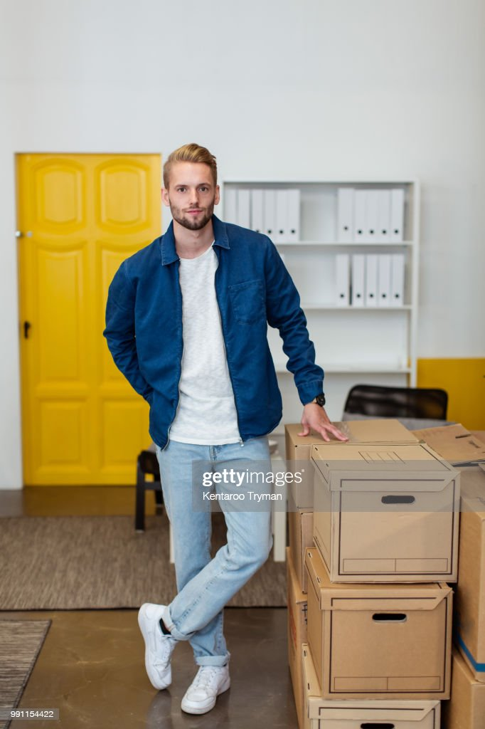 Portrait of confident young businessman standing by cardboard boxes stack at creative office : Stock Photo