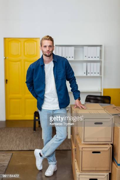 Portrait of confident young businessman standing by cardboard boxes stack at creative office