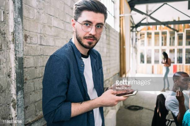 portrait of confident young businessman standing with smart phone against brick wall at creative workplace - junge männer stock-fotos und bilder
