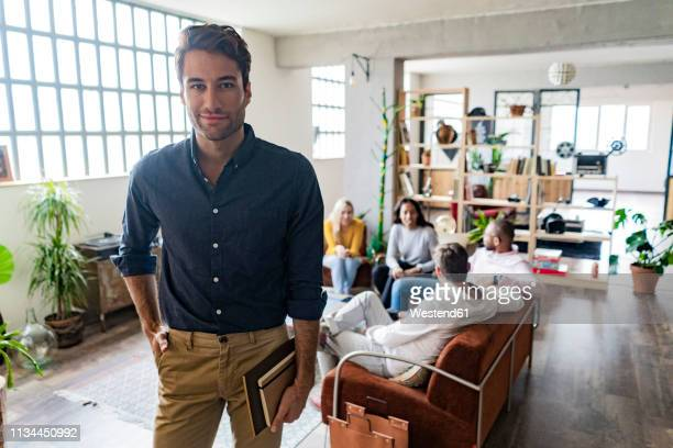 portrait of confident young businessman with coworkers in background in loft office - mains dans les poches photos et images de collection