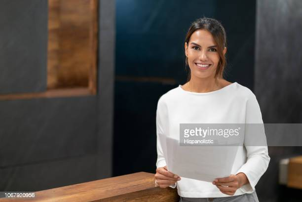 Portrait of confident young businesswoman at the office holding documents and looking at camera smiling