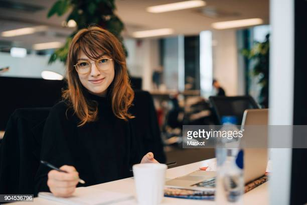 portrait of confident young businesswoman holding pen while sitting at desk in office - professioneel beroep stockfoto's en -beelden