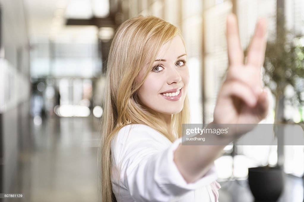 Portrait of confident young businesswoman making victory sign with hand : Stock-Foto