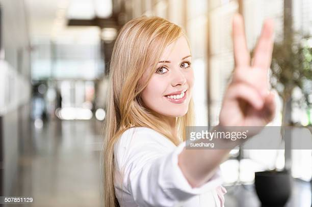 Portrait of confident young businesswoman making victory sign with hand