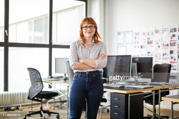 portrait of confident young businesswoman - arme verschränkt stock-fotos und bilder
