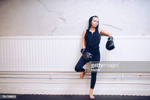 Portrait of confident young female boxer standing against wall at health club