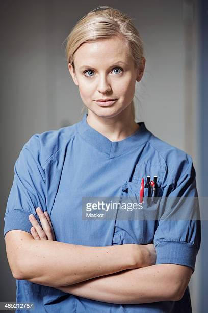 Portrait of confident young female nurse with arms crossed in hospital