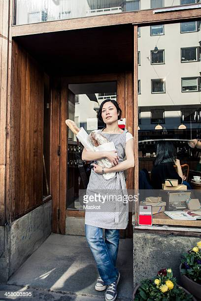 Portrait of confident young female owner holding bread loafs while standing outside bakery