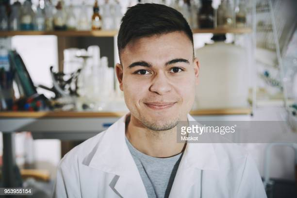 Portrait of confident young male chemistry student standing in college laboratory