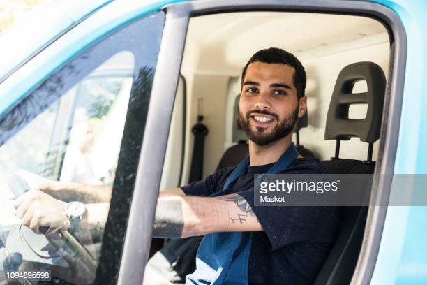 portrait of confident young male owner driving food truck in city - vervoer stockfoto's en -beelden