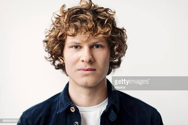 portrait of confident young man against white background - curly stock pictures, royalty-free photos & images