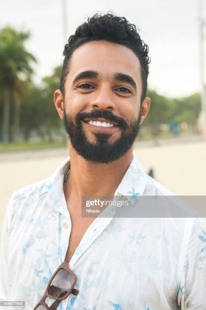 Portrait of confident young man at beach : Stock Photo