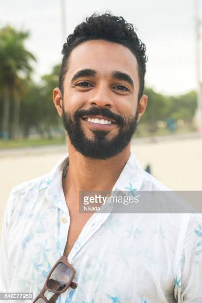 portrait of confident young man at beach - brazilian men stock photos and pictures
