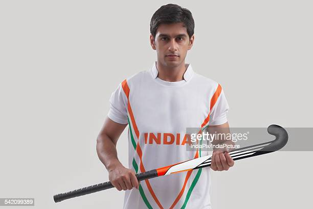 Portrait of confident young man holding hockey stick against gray background