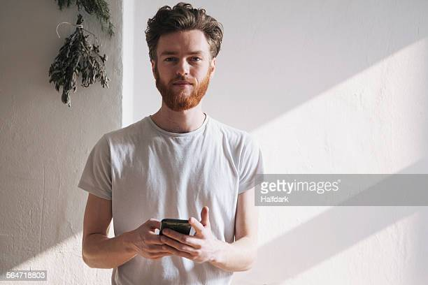 Portrait of confident young man holding mobile phone at home