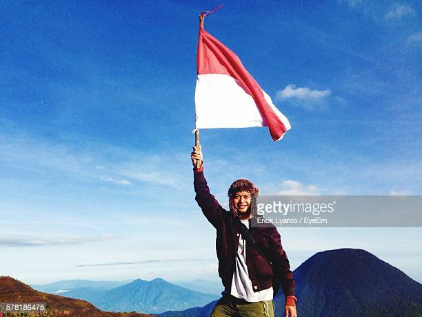 Portrait Of Confident Young Man Holding Monaco Flag On Mountain Against Sky