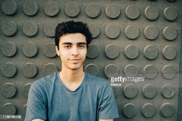 portrait of confident young man standing against wall - 18 19 jahre stock-fotos und bilder