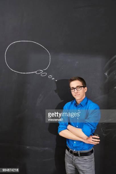 portrait of confident young man standing at blackboard with thought bubble - nur erwachsene fotos stock-fotos und bilder