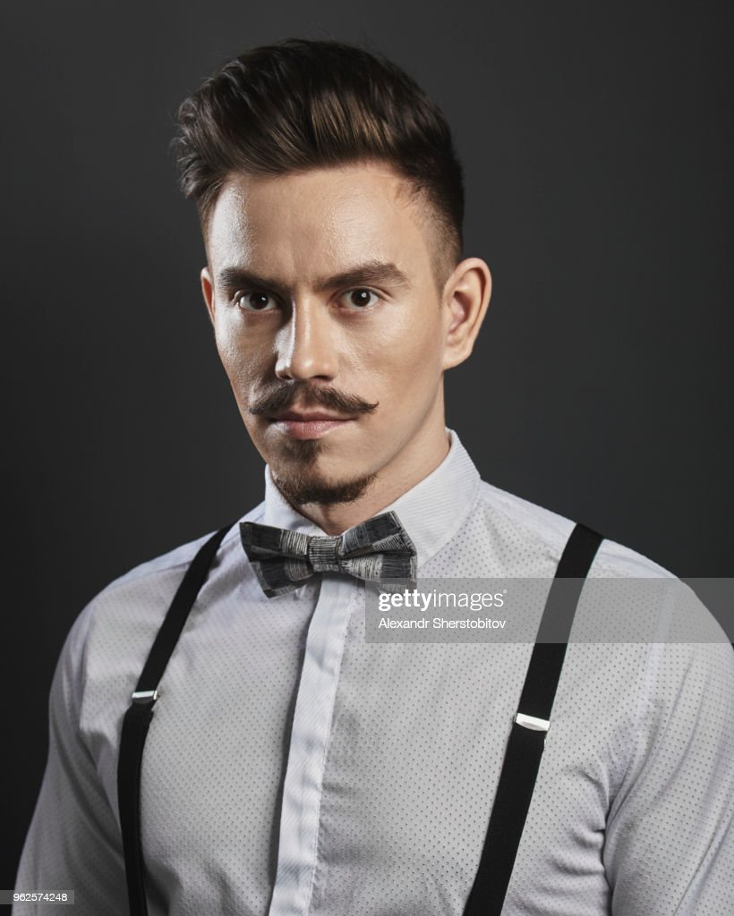 Portrait of confident young man wearing suspenders over gray background : Stock Photo