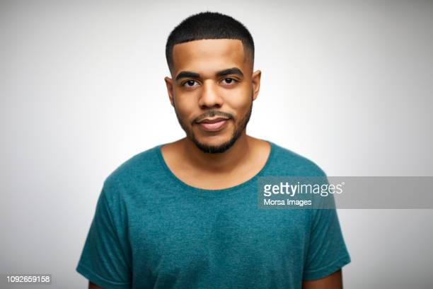 portrait of confident young man wearing t-shirt - human face stock pictures, royalty-free photos & images