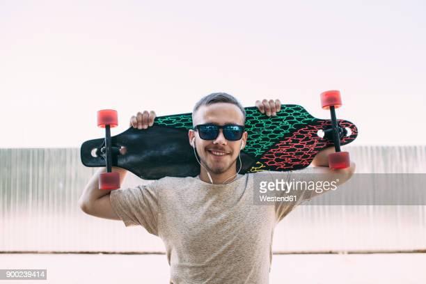 portrait of confident young man with earbuds carrying longboard - patinar fotografías e imágenes de stock
