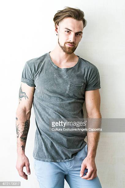 Portrait of confident young man with tattooed arm
