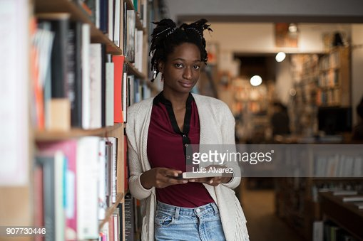 Portrait of confident young woman at bookstore