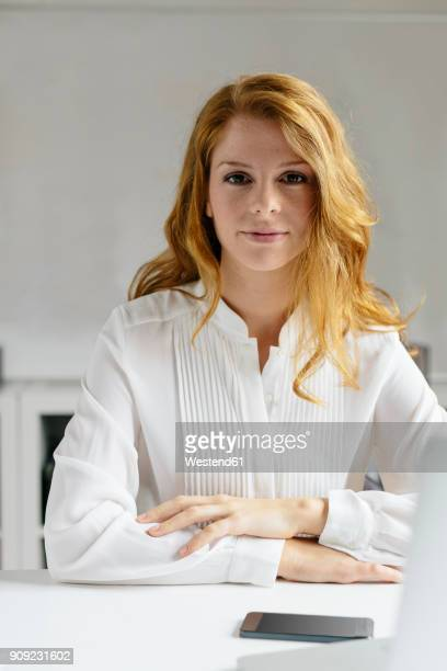 portrait of confident young woman at desk in office - bluse stock-fotos und bilder